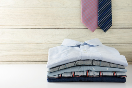 camiseta: Pila de camisas de los hombres y corbata colgando con el fondo de madera blanca Foto de archivo