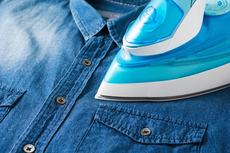 steam iron: Ironing blue denim shirt with steam iron