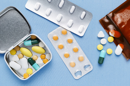Pillen in doos en zak met verpakking van het geneesmiddel op blauwe stof achtergrond