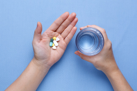 Het nemen van pil met de hand met pillen en glas water Stockfoto