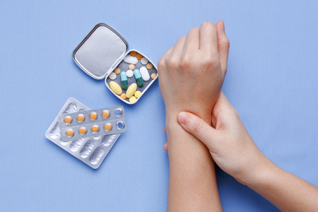 wrist pain: Woman hand with wrist pain and pills on table