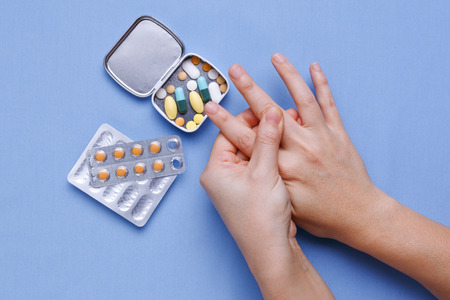 Woman hand with finger pain and pills on table