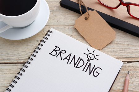 Branding idea concept with notebook and brand tag and coffee on work desk