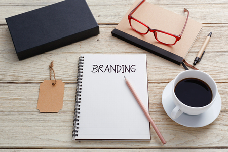 Branding concept with notebook, brand tag, product box , glasses and coffee cup on work desk