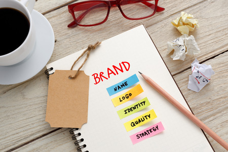 Brand marketing concept with notebook, brand tag and coffee cup on office desk Standard-Bild