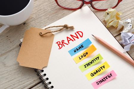 Marca concepto de marketing con el cuaderno, etiqueta de la marca y la taza de café en el escritorio de oficina