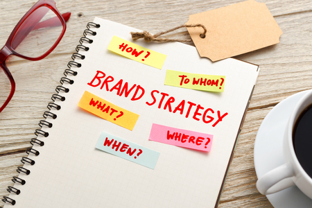 Brand marketing strategy concept with notebook, brand tag and coffee cup on office desk Stock Photo