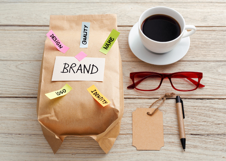 Branding marketing concept with kraft paper bag, brand tag, eye glasses and coffee cup on wood desk