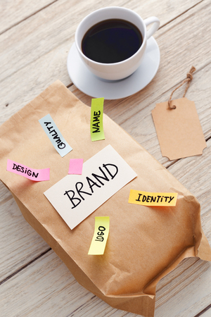 Branding marketing concept with kraft paper bag, brand tag, and coffee cup on wood desk Standard-Bild