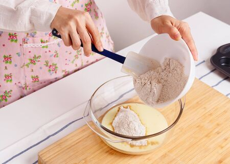 woman baking: Woman baking healthy muffin and pouring flour with ground flaxseed into milk and baking ingredients Stock Photo