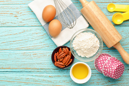 Baking cupcake with ingredients flour eggs pecan nut olive oil and rolling pin from above for background with space