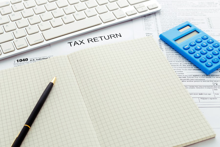 keyboard: Tax return form with computer keyboard and pen on notebook