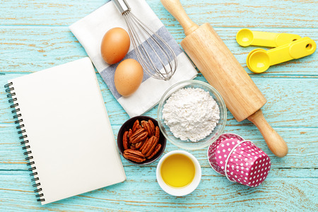 Baking background with black notebook and baking ingredients