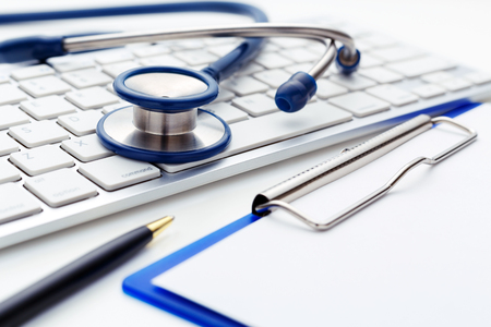 stethoscope exam: Medical concept with stethoscope on computer keyboard with clipboard Stock Photo