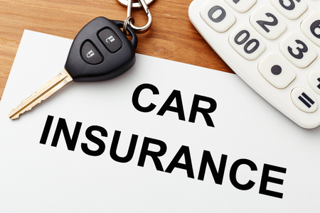 Car insurance with car key and calculator on wood table Stock Photo