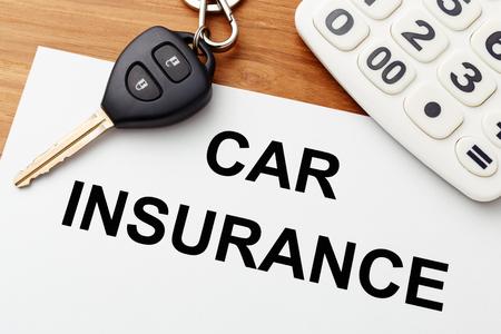 Car insurance with car key and calculator on wood table Standard-Bild