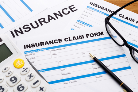 Insurance claim concept with pen and calculator Standard-Bild