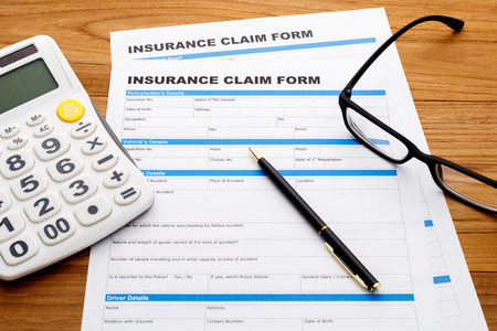Insurance claim form with pen and calculator on wood desk