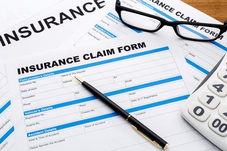reimbursement: Insurance claim form with pen and calculator on wood desk