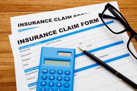reimbursement: Insurance claim concept with pen and calculator on wood desk