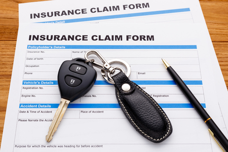 motor vehicle: Insurance claim form with car key and pen on wood desk Stock Photo