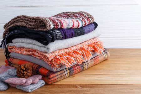 checkered scarf: Winter fashion clothing with scarft gloves and blanket  with wood background Stock Photo