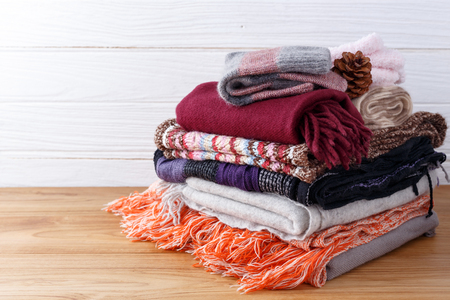 Winter fashion clothing stack with scarft gloves and blanket with wood background