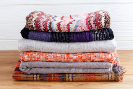Winter fashion clothing stack with scarft gloves and blanket Standard-Bild