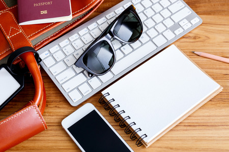 Travel booking and planning concept with bag sunglasses phone and notebook