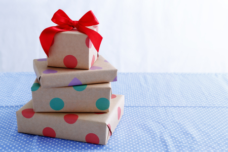 Presents for birthday with red bow on table with space