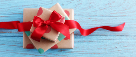 birthday presents: Presents for birthday with red bow and ribbon on wood table Stock Photo