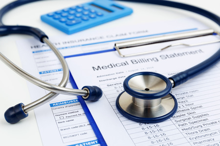 Stethoscope on medical bills and health insurance claim form