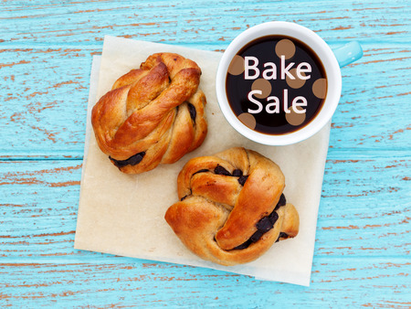 bake sale: Bake sale with bread roll and coffee cup on wood background