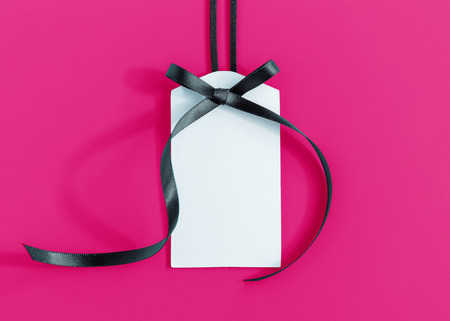 Gift tag with ribbon on pink background