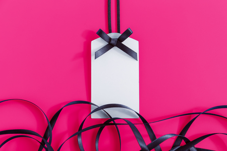 Gift tag with black ribbon on pink background