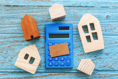 Wood houses and calculator with blank brown card for housing loan concept Standard-Bild