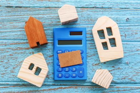 Houten huizen en rekenmachine met lege bruine kaart voor huisvestingsconcept