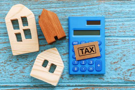 Houten huis met calculator voor vastgoedbelasting concept Stockfoto