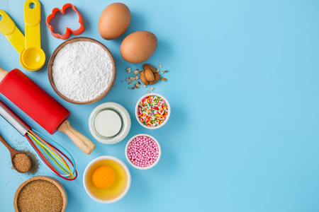 Baking background with ingredients eggs, flour, milk, sugar and cake decor on light blue table