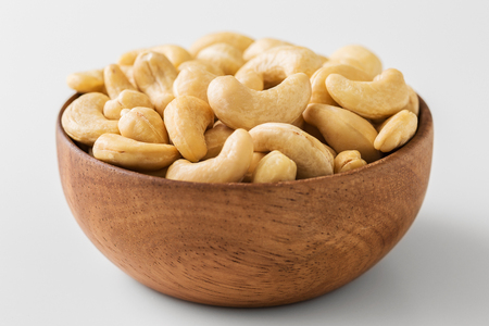 Raw cashew nut in wooden bowl closed up
