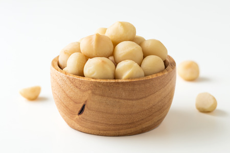 Macadamia nuts in wooden bowl on white background