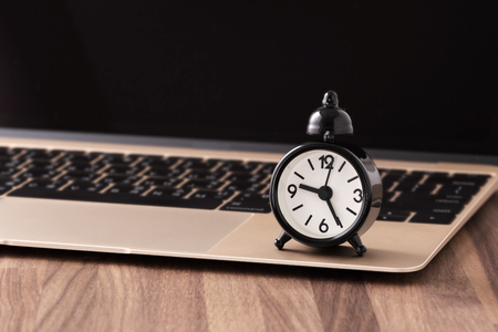 Time management concept with clock on computer Stock Photo