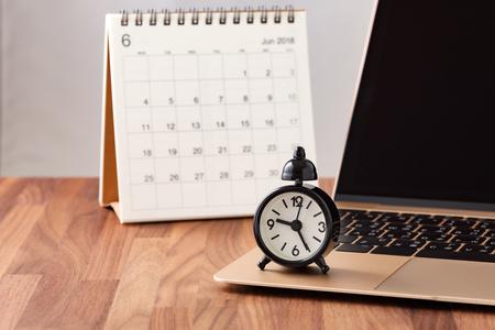 Concepto de gestión del tiempo con calendario y reloj en computadora en mesa de madera Foto de archivo