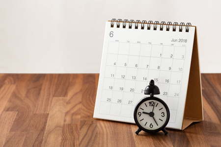Time management concept with calendar and clock on wooden table Stock Photo