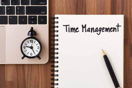 Time management concept with clock on computer, notebook and pen