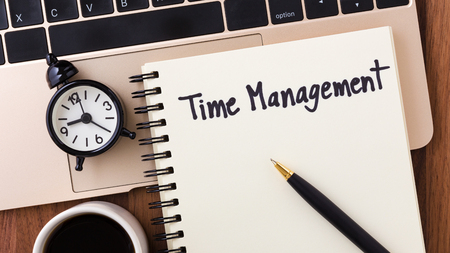 Time management concept with notebook, clock and pen on computer from top view Stock Photo