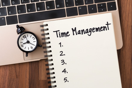Time management concept with list on notebook and clock on computer from top view Stock Photo