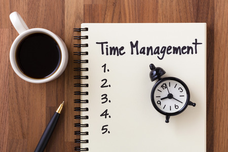 Time management concept with list on notebook, clock and coffee cup from top view Stock Photo
