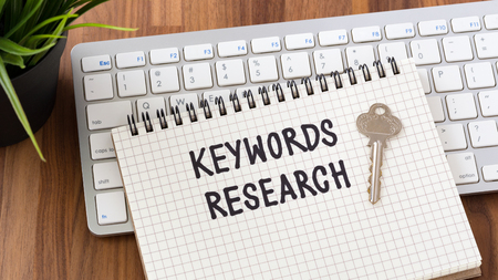 Keywords research words on notebook with key computer keyboard