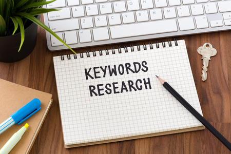 Keywords research words on notebook with computer